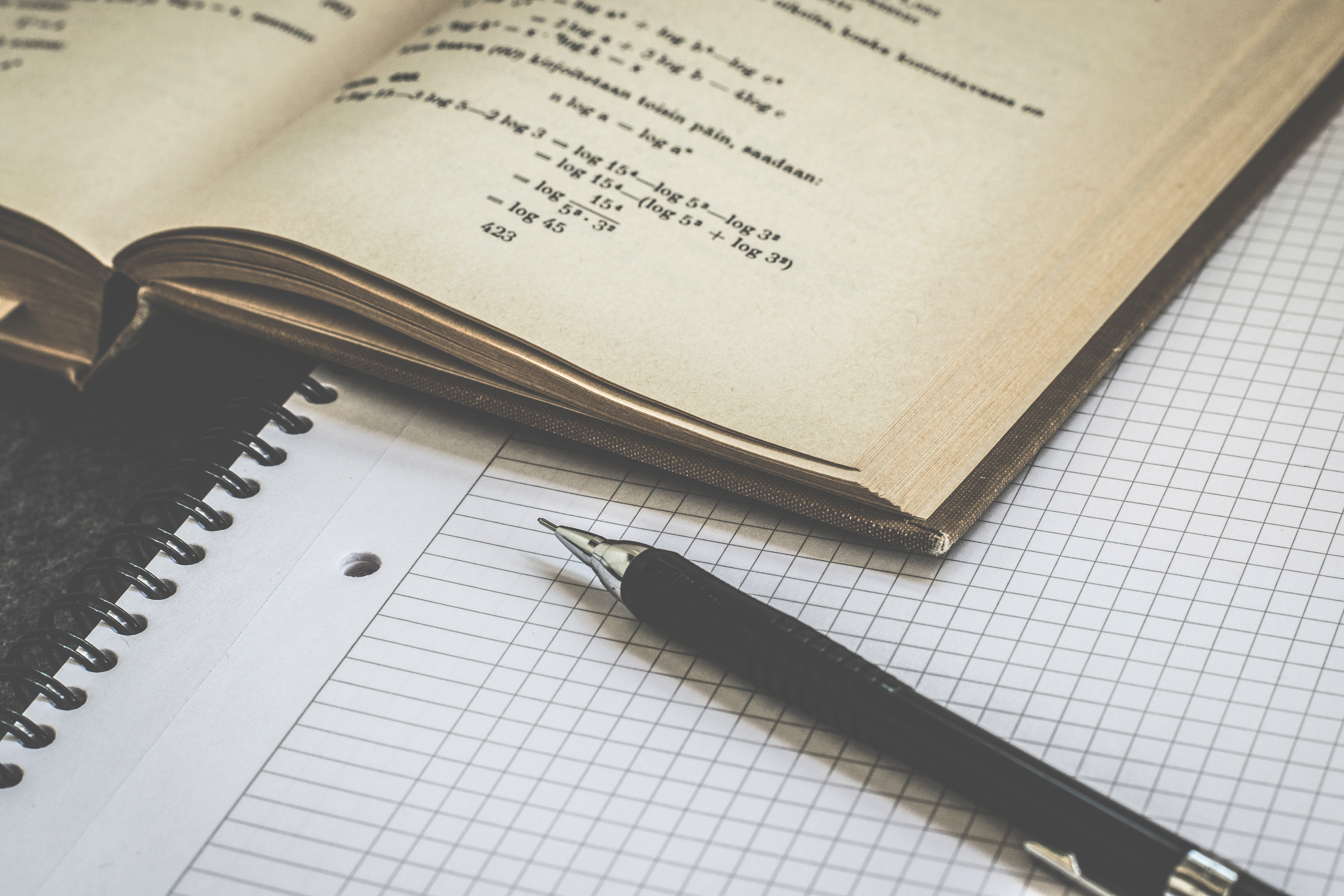 A pen and some graph paper next to an open book with mathematics in